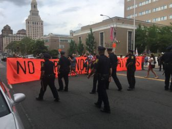 Hartford police officers approach a protester holding a banner that block a portion of Main Street Monday.