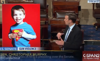 Sen. Chris Murphy displays a poster of Newtown shooting victim Dylan Hockley as he comes to the end of his filibuster on the Senate floor early Thursday.