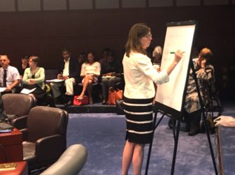 Consultant Megan Burns of Bailit Health writes on a sketchpad during a discussion with the Health Care Cabinet.