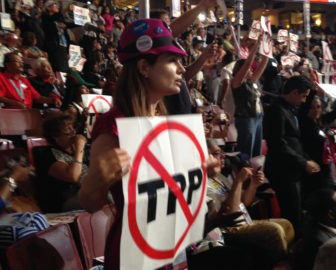 Connecticut Sanders delegate Mercedes Alonso holds up a sign opposing the Trans-Pacific partnership trade pact on the first day of the convention.