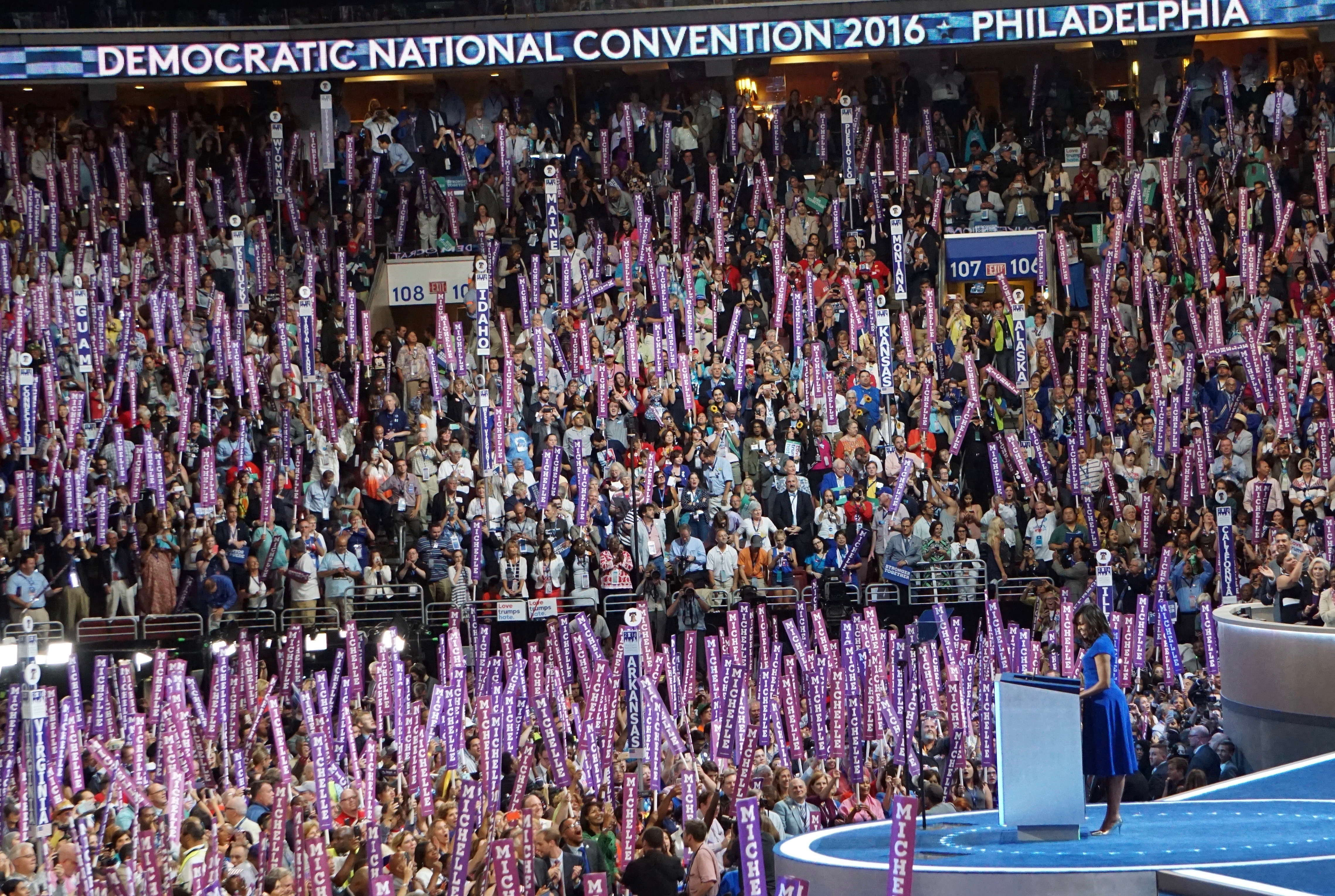 """Michelle Obama at the podium among a sea of purple """"Michelle"""" signs."""
