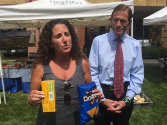 Tara Cook-Littman, left, and U.S. Sen. Richard Blumenthal, right. Cook-Littman is holding two products with GMO labels.