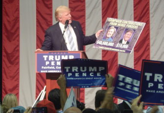 Republican presidential candidate Donald J. Trump holds a sign he said showed how little he had received in contributions from people who work at hedge funds compared to Hillary Clinton.