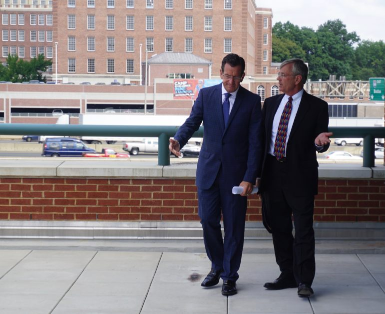 Gov. Dannel P. Malloy and Transportation Commissioner consult before a press conference by the I-84 viaduct.