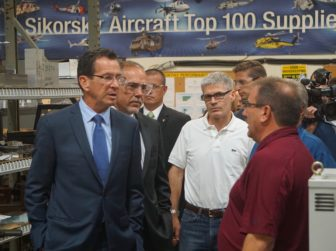 Gov. Dannel P. Malloy and House Majority Leader Joe Aresimowicz listening to a Sikorsky supplier, Mark Labbe, right.