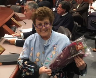 State Rep. Betty Boukus cradles a bouquet of roses at the State Bond Commission meeting Tuesday.