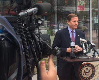 U.S. Sen. Richard Blumenthal at a portable lectern on a sidewalk outside Toy Chest,