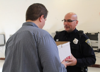 Officer Vic Fuentes delivers needed ballots to Moderator Ryan Munden at Wilbur Cross High School.