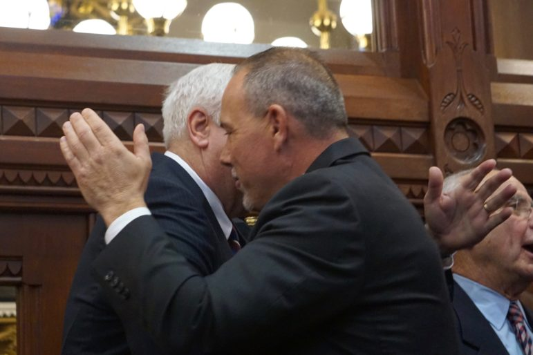 House Speaker Joe Aresimowicz embraces a predecessor, Thomas D. Ritter, the father of House Majority Leader Matt Ritter.