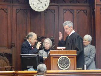Senate President Pro Tem Martin M. Looney takes the oath of office from Superior Court Judge Brian T. Fischer, a longtime friend who recently donated a kidney to Looney. Looking on is Looney's wife, Ellen.