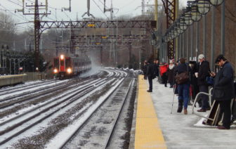 A northbound Metro North train pulls into the Darien train station as commuters wait for the next train into New York on the southbound platform.