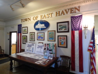 An art display in East Haven Town Hall between two American flag banners.