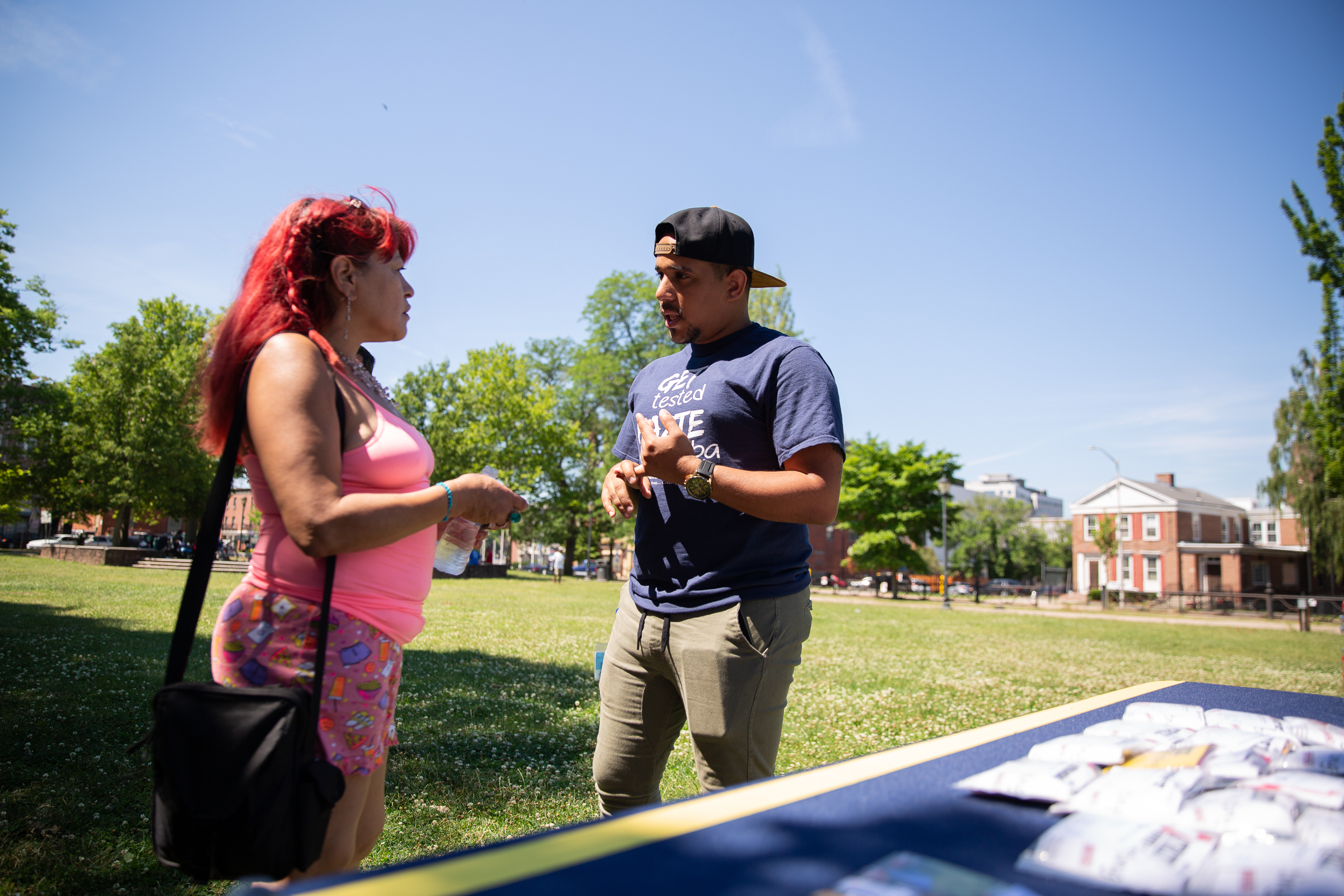 Community Renewal Team's Jovany Rolon speaks to Carmen Cruz about PrEP medication for HIV prevention in Hartford's Barnard Park. Photo by Ryan Caron King