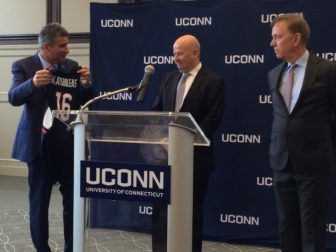 Uconn president-designate Tom Katsouleas accepts a UConn jersey from Uconn Board of Trustees President Tom Kruger and Gov. Ned Lamont