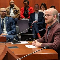 Conor Pfeifer, a development officer with Triangle Community Center. voices support for a bill to establish a Lesbian, Gay, Bisexual, Transgender and Queer Health and Human Services Network. Rep. Raghib Allie-Brennan, at left, co-proposed the bill.