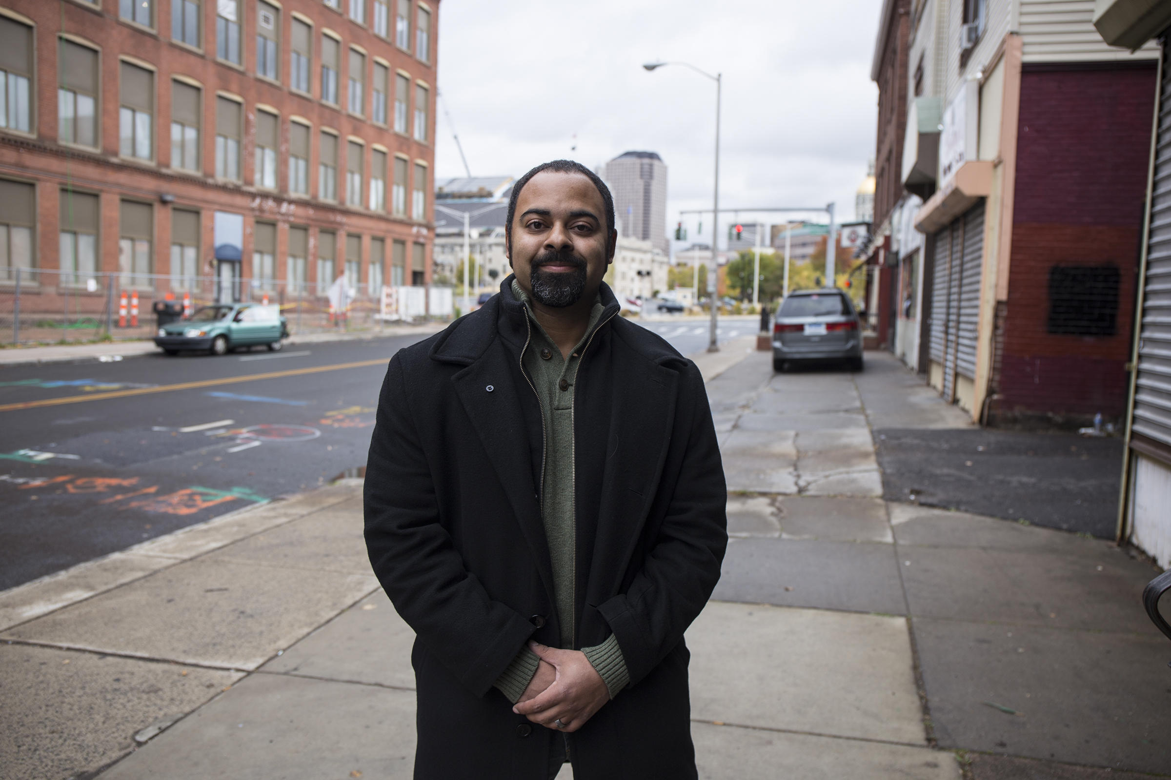Aaron Gill on the sidewalk outside the building he purchased and renovated with his wife on the edge of the historic Frog Hollow neighborhood in Hartford. Gill is the leader of the local neighborhood advisory board and a member of Hartford's Planning and Zoning Commission.
